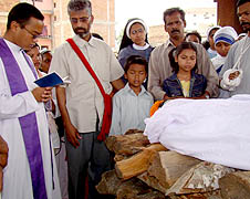 Catholic priests blessing the body of a Catholic on the funeral pyre