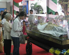 People praying before the relics of Saint John Bosco