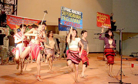 Members of an indigenous people's group stage a show for peace