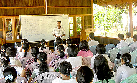 Charles Kyaw Zin Hteik teaching English to youths in the education center of the monastery