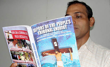 A Priest is reading the 'Report of the People's Tribunal Enquiry'