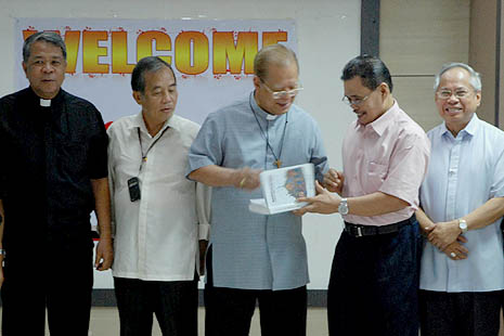 MILF peace panel chair Mohagner Iqbal gives a book to Davao Archbishop Fernando Capalla after the meeting