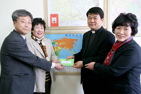 The faithful of the Eunhaeng-dong Holy Family Chruch is delivering the fund to a priest (photo courtesy of Suwon diocese)