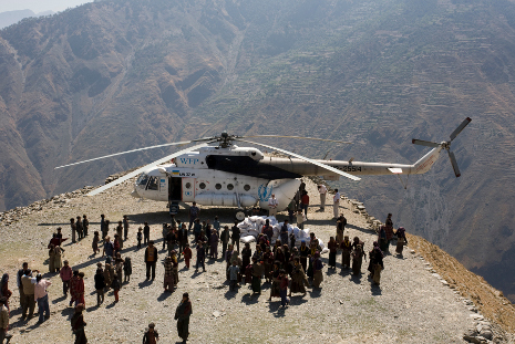 Nepalis in the remote hills gather round the UN helicopter as it unloads rice