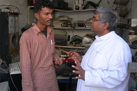 Brother Khushi Lal (right) speaking to an HIV victim helped by Caritas Pakistan