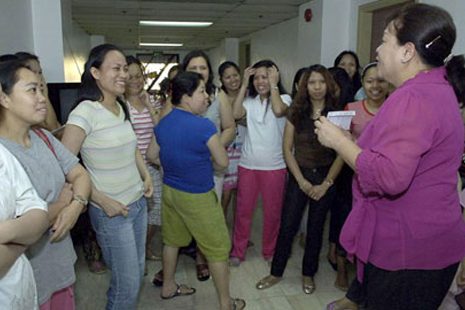 A government official talks to repatriated overseas domestic workers who escaped from their employers