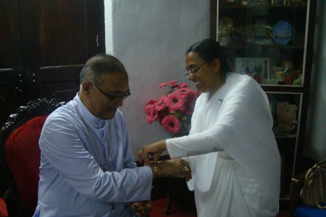 Brahma Kumari tying the sacred thread on the wrist of Bishop Aloysius Paul D'Souza of Mangalore on August 13