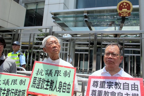 Cardinal Joseph Zen Ze-kiun of Hong Kong, center, attends a protest in front of the Central Government liaison office today