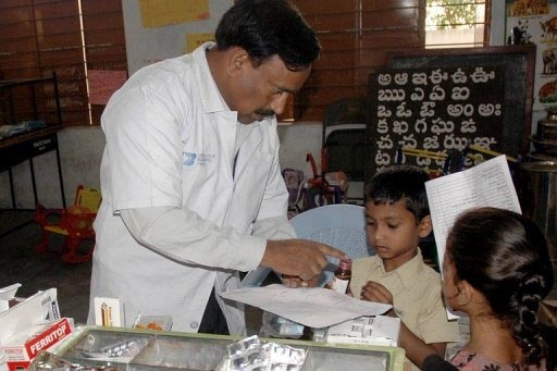 A doctor in India distributes medicine