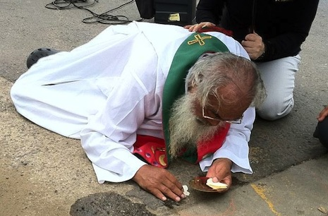 Fr Mun attempts to retrieve the Eucharist after allegedly being knocked to the ground by police (Photo courtesy of Gangjeong village)