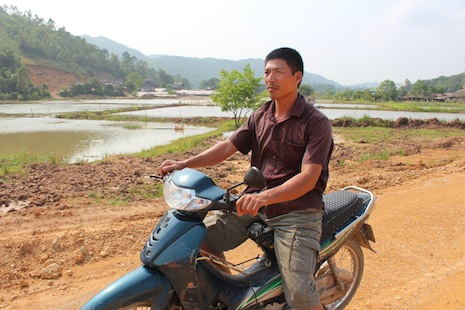 A farmer looks at his former land reclaimed by the government for a highway project