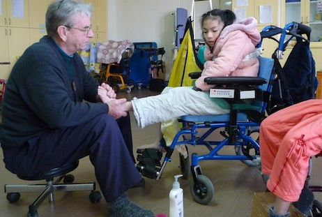 Fr Josef Eugster uses reflexology to treat a young patient