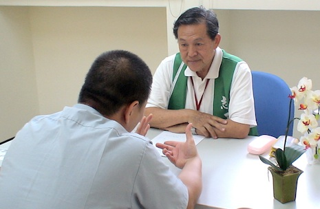 A priest talks to an inmate during a prison outreach visit