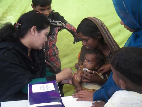 A child is vaccinated at a temporary Caritas clinic in Karachi