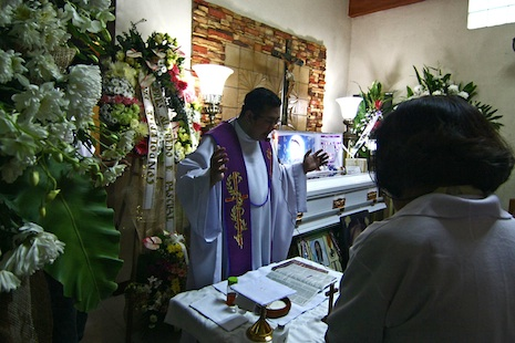 A priest celebrates Mass at a wake for Kristel Tejada (photo by Vincent Go)