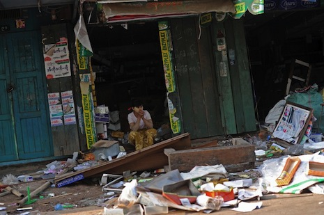 A Muslim woman outside her shop which was wrecked during rioting in Okkan on May 1 (Picture: AFP)