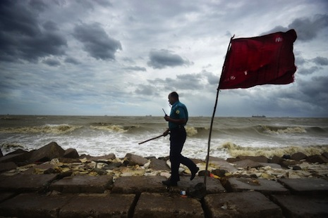 <p>A Bangladeshi police officer clears a beach in Chittagong on Thursday as Cyclone Mahasen moved closer to landfall (AFP photo/Munir Uz Zaman)</p>