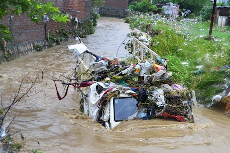 <p>Trash covers a truck submerged in flood waters in Dehradun in Uttarkhand (AFP photo)</p>