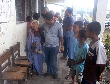 <p>Minister Jacinto Rigoberto talks to an elderly flood victim at an emergency shelter</p>