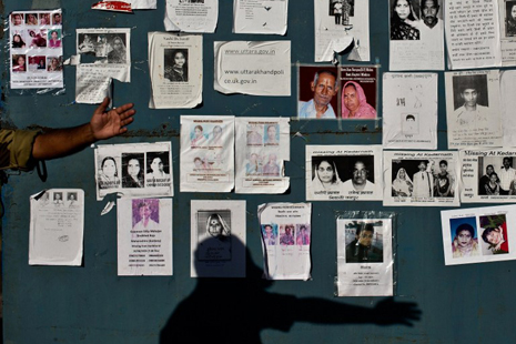 <p>A man gestures in front of pictures of the missing from India's floods (AFP photo/Manan Vatsyayana)</p>
