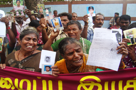 <p>Family members of those who went missing during the war hold up pictures of lost relatives in Jaffna</p>