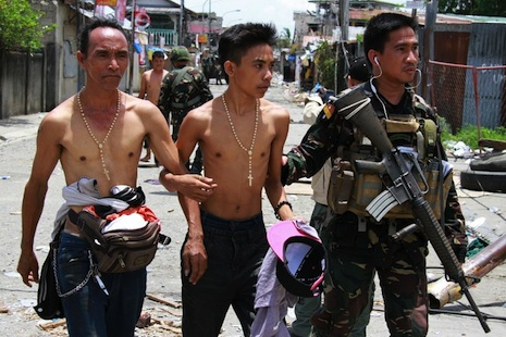 <p>A soldier escorts two hostages from the site of a standoff in Zamboanga (AFP photo)</p>
