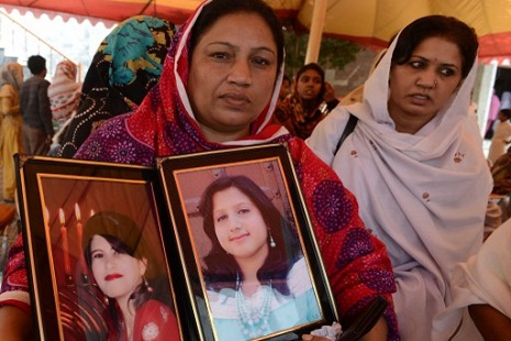 <p>A Christian woman holds pictures of her relatives killed in the Peshawar suicide bombing (AFP/A Majeed)</p>