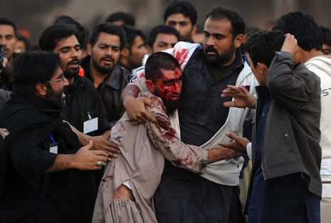 <p>Shiites assist an injured Sunni Muslim during the clashes (picture: AFP Photo/Aamir Qureishi)</p>