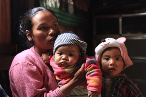 <p>Ling Mang sits with two of her children inside her home on the edge of Kampetlet, Chin state.</p>