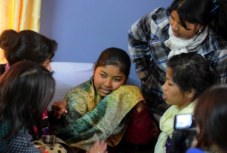 <p>Indentured &quot;kamlari&quot; girl Jujri Tharu, center, speaks to rights activists after being rescued from her workplace (picture: AFP Photo/Prakash Mathema)</p>