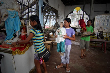 <p>Parishioners return religious images to a destroyed Catholic Church in Leyte. (Picture by Vincent Go)</p>