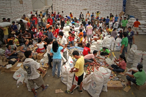 <p>Residents in devastated areas find temporary work repacking relief goods in government warehouses (photo by Vincent Go)</p>