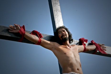 <p>A penitent is nailed on a cross in the province of Pampanga. (Photo by Joe Torres)</p>