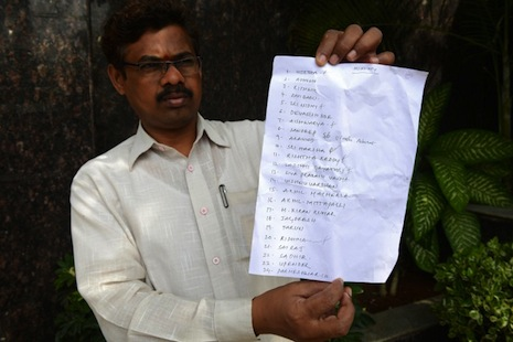 <p>A parent holds up a list of names of students who are feared to have drowned in the incident. Picture: AFP Photo/Noah Seelam</p>