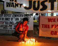 A Filipino journalist lights candles in memory of colleagues who died during the Nov. 23, 2009 massacre