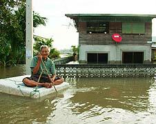 Một ông già ngồi trên một tấm bê tông bao quanh bởi nước lũ